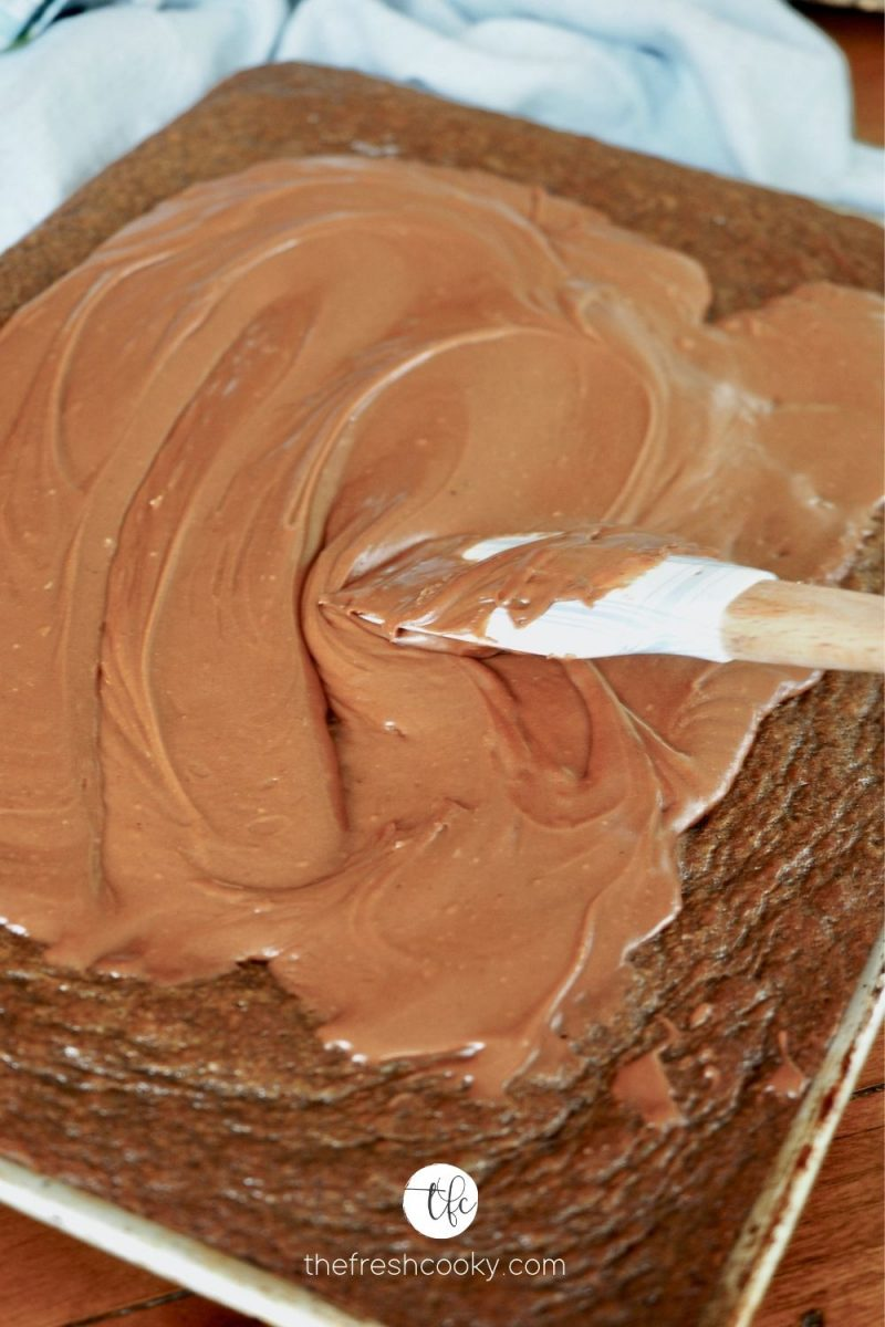 A spatula smoothing on cooked fudge frosting onto the top of a Texas Chocolate Sheet Cake.