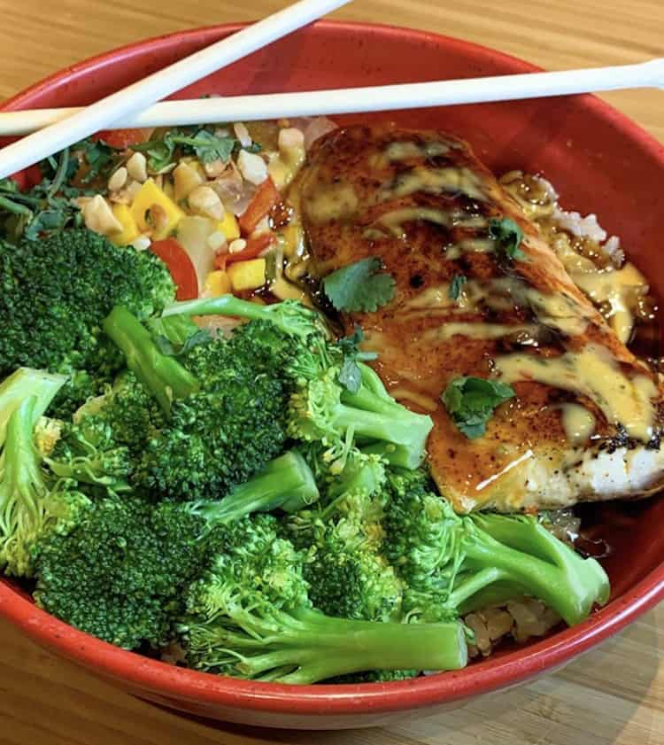 red bowl filled with brown rice, steamed broccoli a corn salsa, mahi-mahi grilled fish with Teriyaki Sauce and chopsticks crossed atop the bowl.