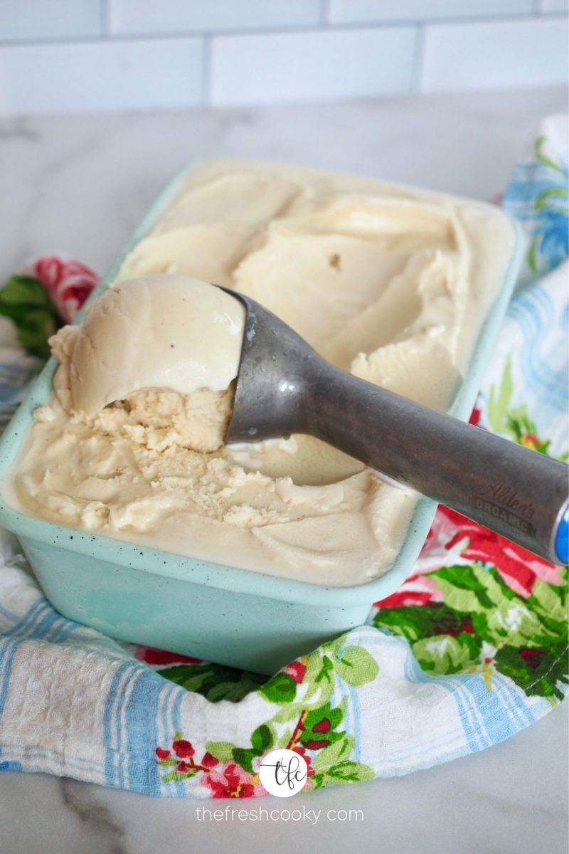 Ice cream scoop in container of homemade old fashioned vanilla ice cream with pretty tea towel around.