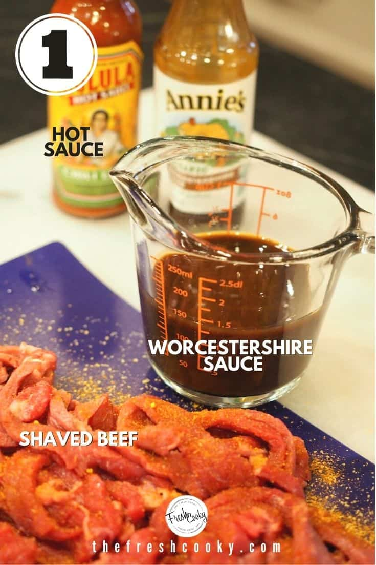 ingredient image with left to right, Cholula hot sauce, Annie's Worcestershire sauce, glass measuring cup with worcestershire sauce and thinly sliced steak seasoned on blue cutting board.