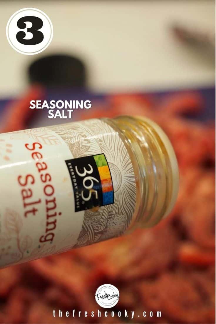 Sprinkling thinly sliced steak with a jar of 365 Seasoning Salt.