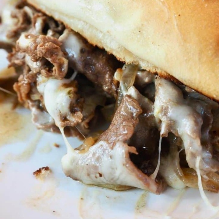 cheesesteak sandwich oozing tender, thinly sliced beef, stringy cheese, juices and caramelized onions with a toasted sub roll
