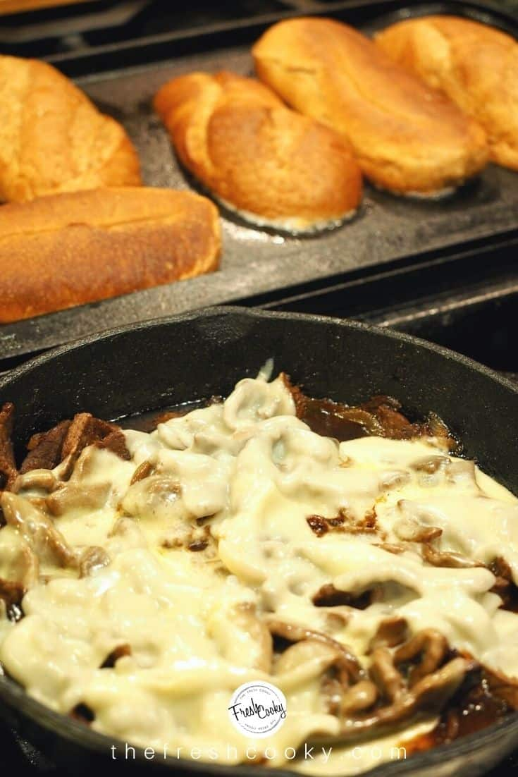 Skillet filled with melty cheesesteak with griddle in background toasting sub sandwich rolls
