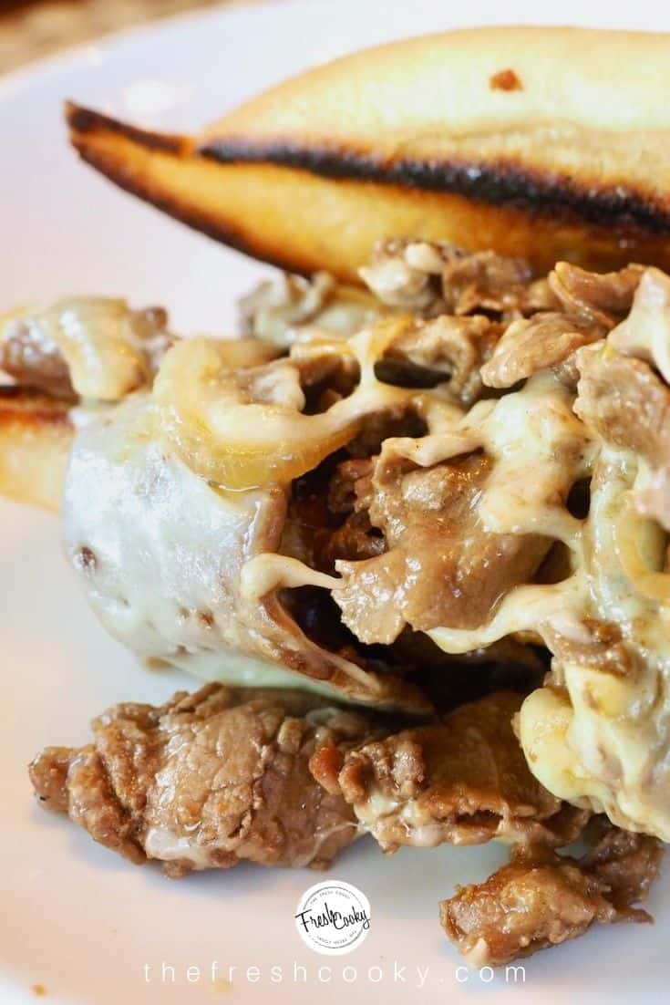 close up image of half cheesesteak sandwich on white plate, with toasted sub roll and stuffed with steak, melted cheese and sauteed onions.