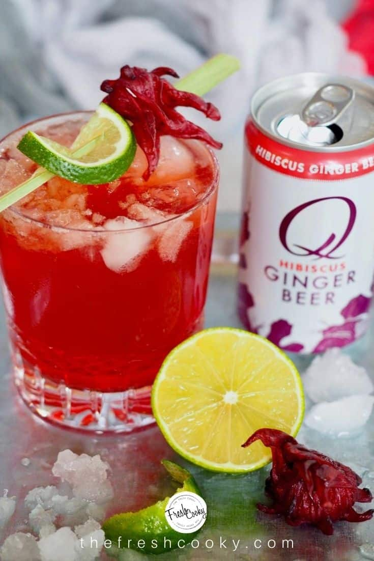 Shot of Red cocktail in crystal glass, a Dark & Stormy cocktail with a can of Q Mixers Hibiscus Ginger Beer a lime and ice.