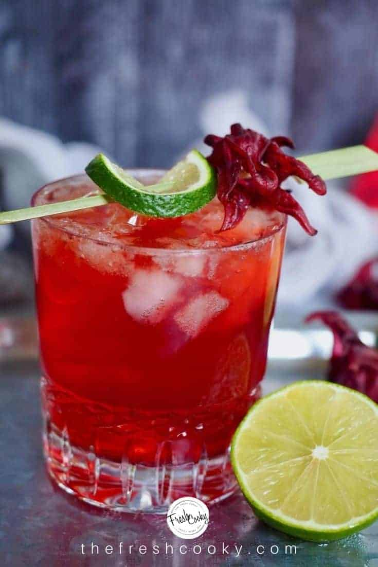 crystal glass filled with red liquid, hibiscus ginger beer, dark rum and lime. with a wedge of lime. Garnished with a bamboo stick, lime and hibiscus flower