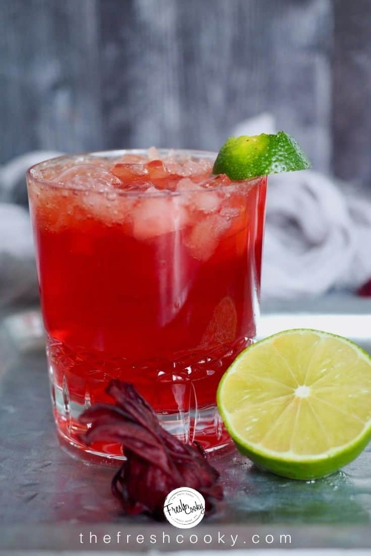 top shot of glass with hibiscus ginger beer, rum and lime with a half a lime and hibiscus flower