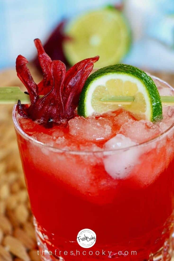 Alt Text top shot of glass with hibiscus ginger beer, rum and lime with a half a lime and hibiscus flower