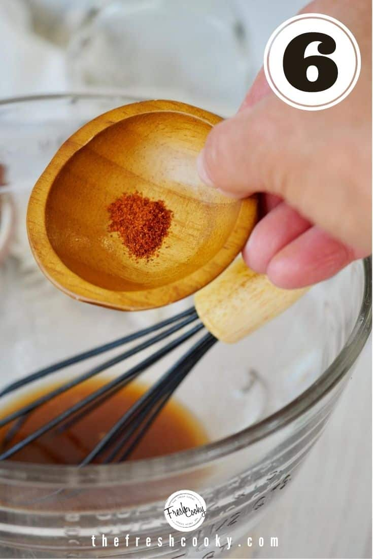 small wooden bowl with cayenne pepper going into mixing bowl with whisk in background