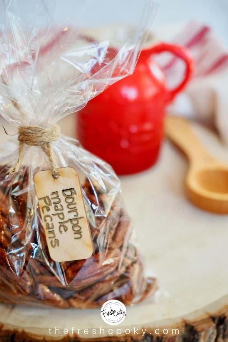 cello bag filled with maple bourbon pecans tied with twine with a wooden tag handwritten Bourbon Maple Pecans sitting on sliced wood piece with red syrup jar and wooden tablespoon in background.