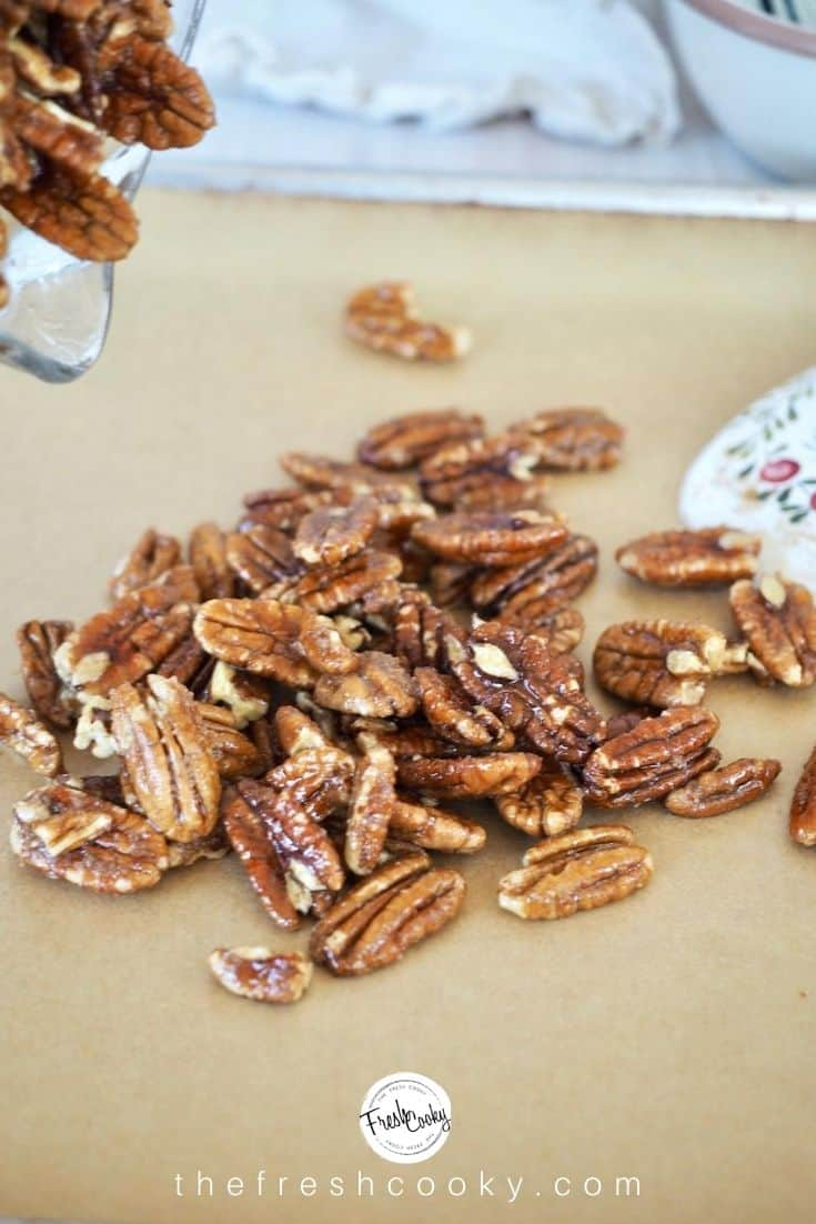 pouring pecan halves onto parchment lined baking sheet that have been mixed with slurry