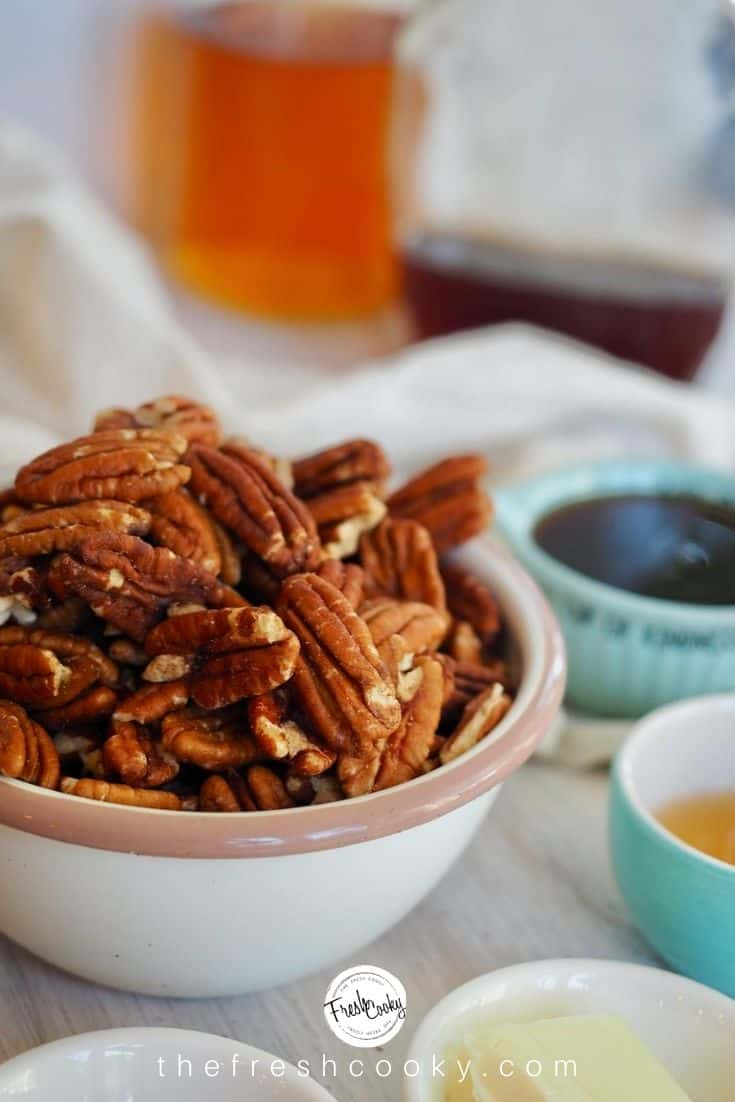 close-up shot of raw pecan halves in small bowl, with maple syrup and bourbon in background.
