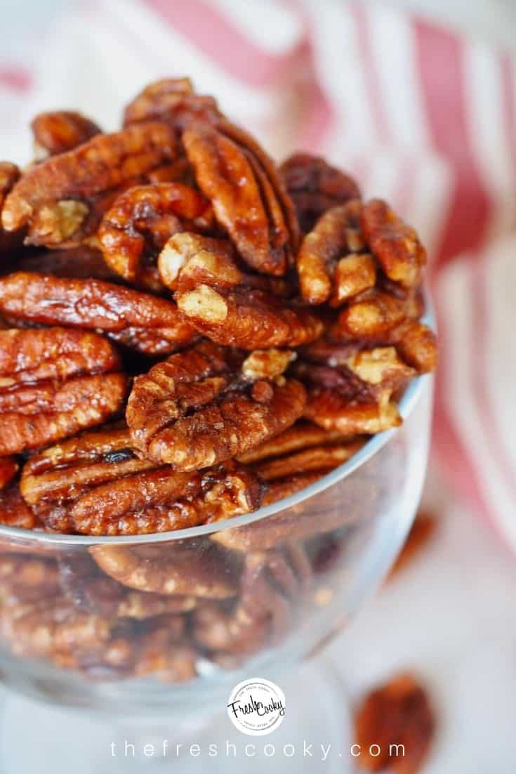 close up shot of maple bourbon candied pecans in glass bowl with red and white striped tea towel in background