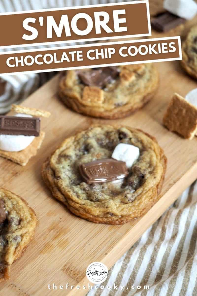 Pinterest Image for s'more chocolate chip cookies with image of cutting board and 3 s'more stuffed chocolate chip cookies sitting on top, with two stacks of s'more ready to stuff in more cookies.