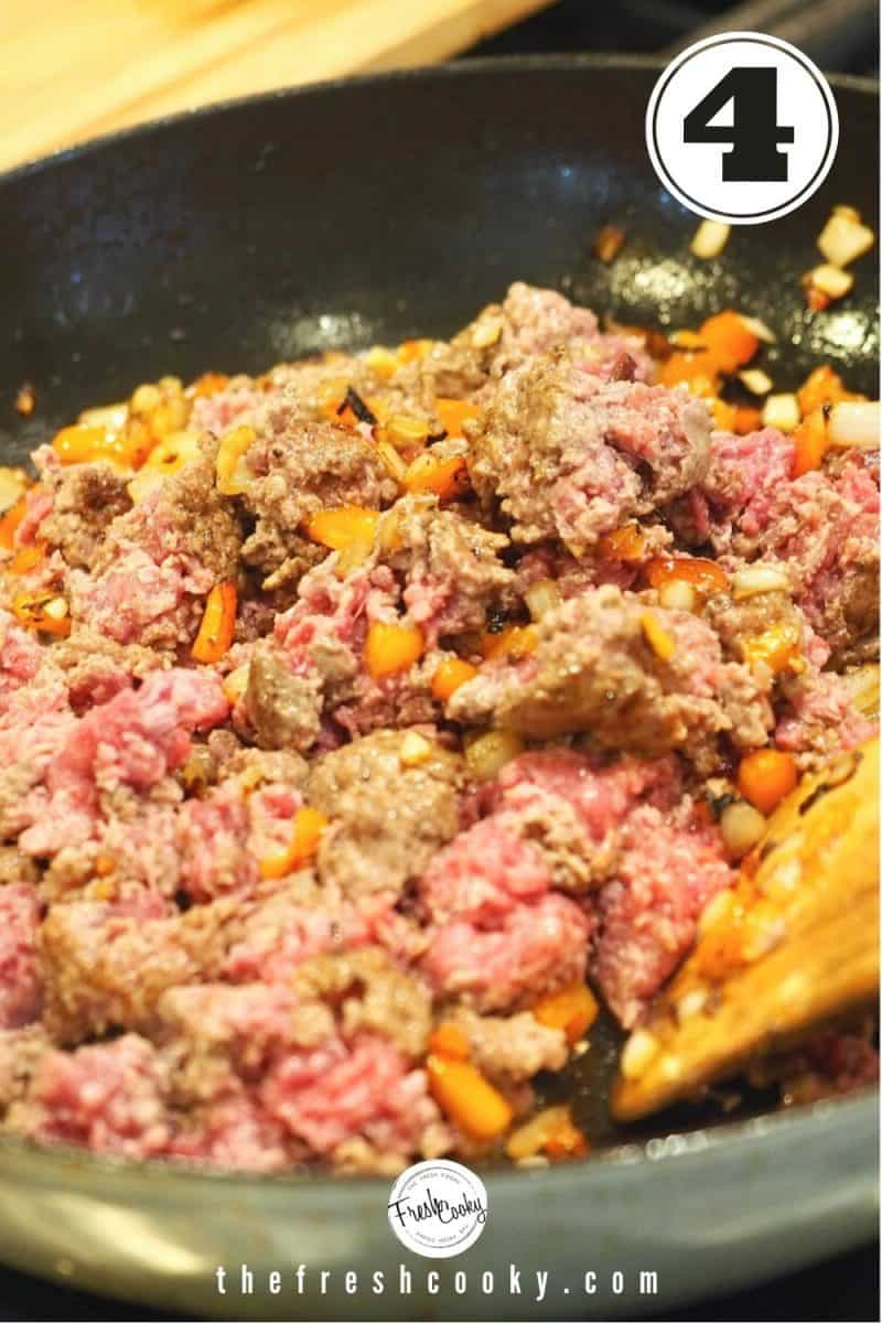Wooden spoon in skillet stirring mixture of browned ground beef and veggies for sloppy joes