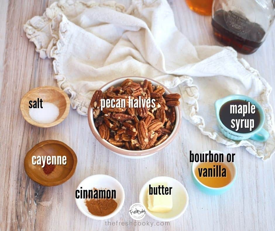 Left to right, ingredient image for Maple Bourbon Pecans. Salt, cayenne pepper, cinnamon, butter, bourbon, maple syrup and pecans, on wood with neutral colored napkin and bottles of maple syrup and bourbon in background.
