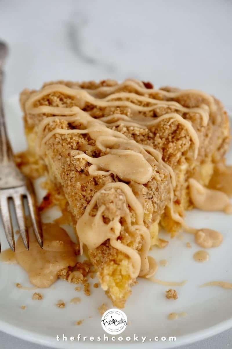 Image of wedge of apple crumb cake closeup with fork on left side sitting on a white plate on top of a white marble slab.