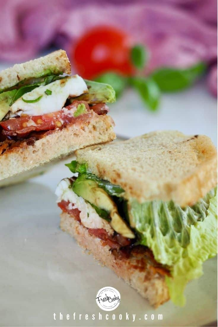 Sourdough bacon, lettuce, tomato Caprese sandwich, cut in half with basil, mozzarella cheese and balsamic vinegar.
