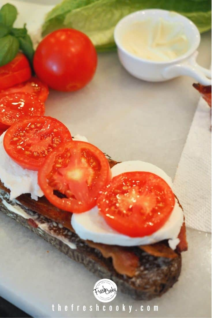 Pumpernickel toast with mayo, bacon, slices of mozzarella cheese and three slices of tomatoes on top. Background has small bowl of mayo and a whole tomato with some romaine lettuce leaves.