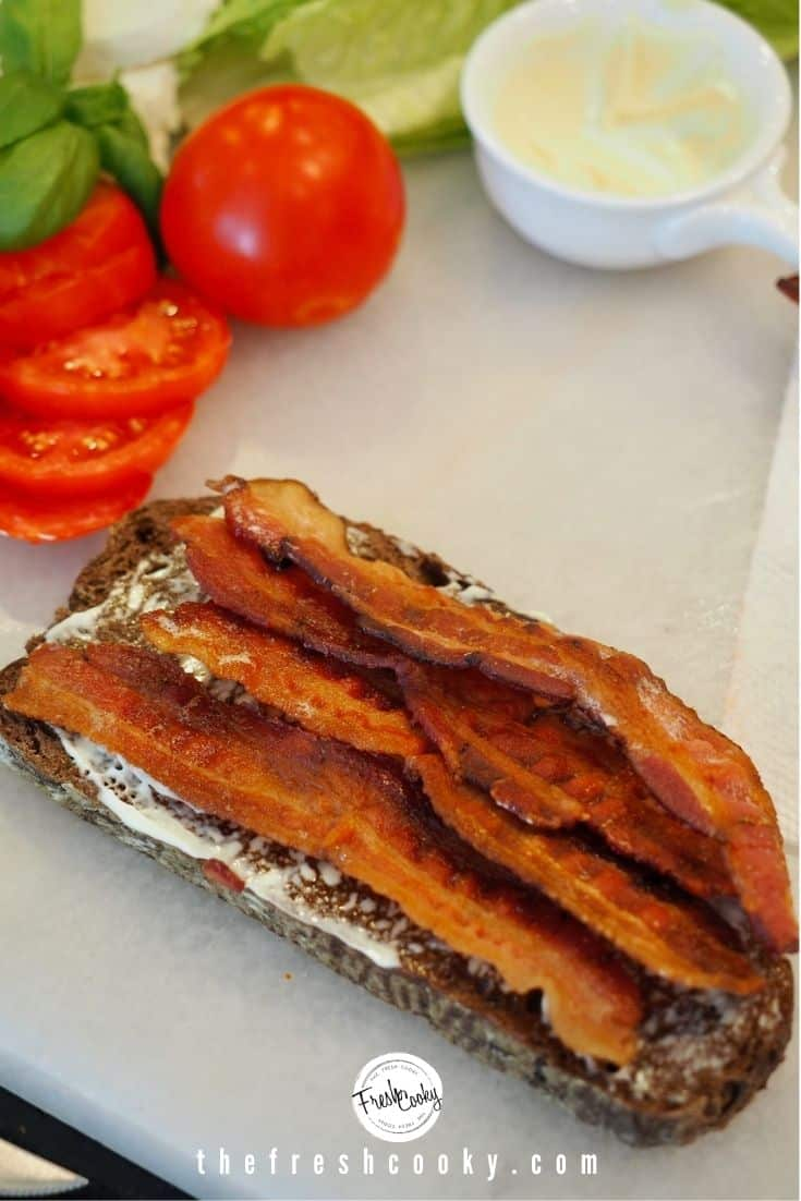 4 slices of crisp bacon on a slice of pumpernickel toast with mayo, slices of tomatoes and basil in background.