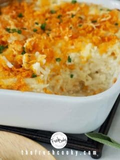 Recipe image of white baking dish filled with cheesy funeral potatoes with a scoop removed.