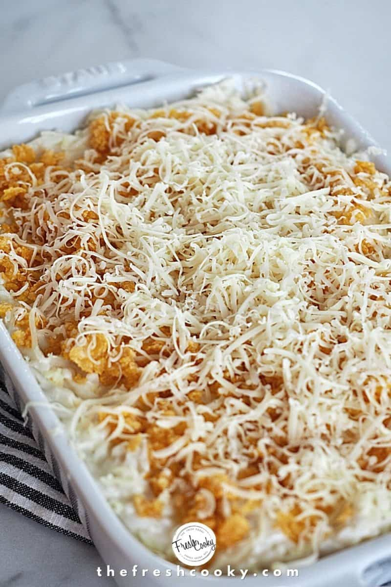 Cheesy Funeral Potatoes ready for the oven with a fresh grate of cheddar cheese on top