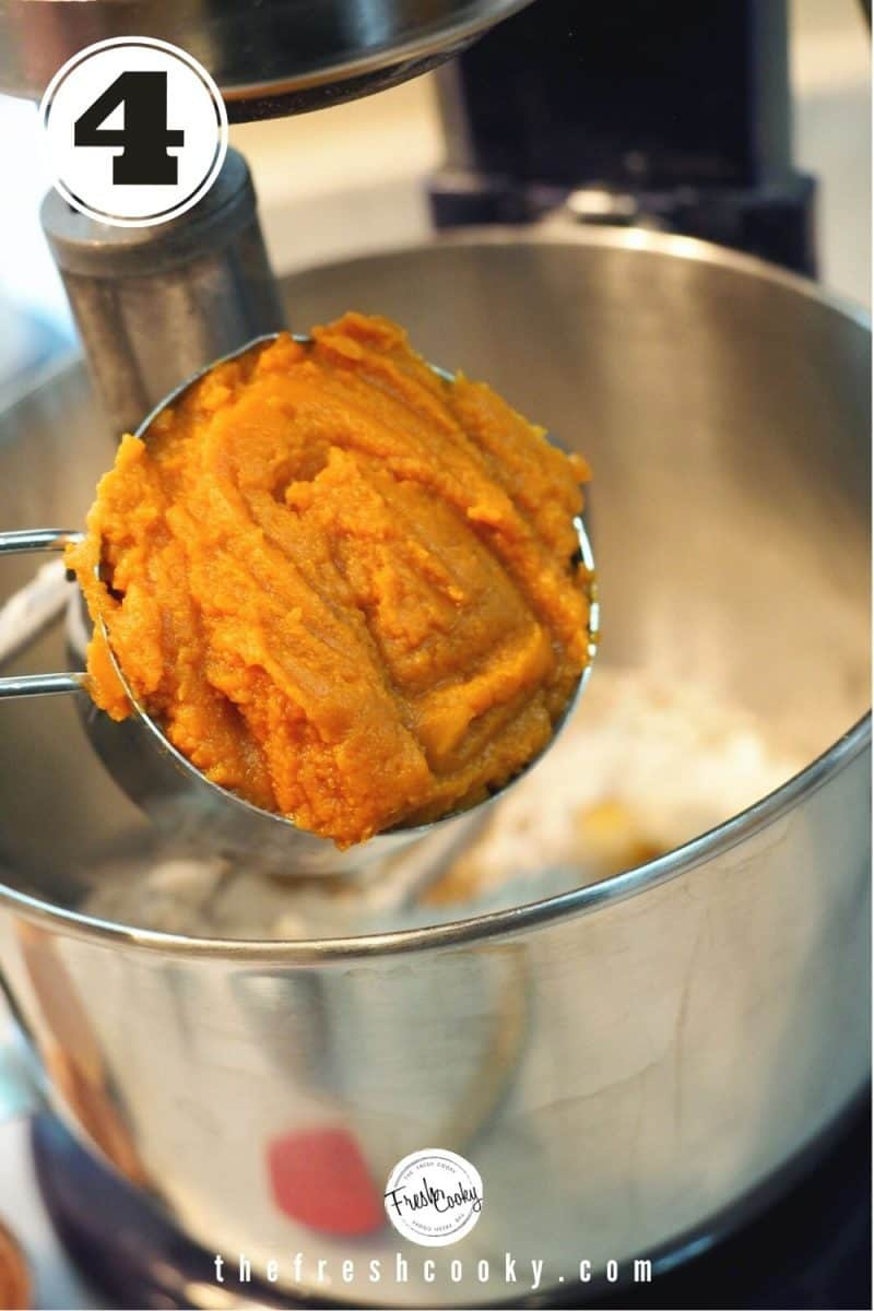 rounded ¾ cup of pumpkin pure over mixing bowl of stand mixer