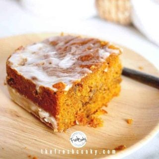 horizontal image of slice of pumpkin spice cake sitting on a bamboo plate with fork behind.