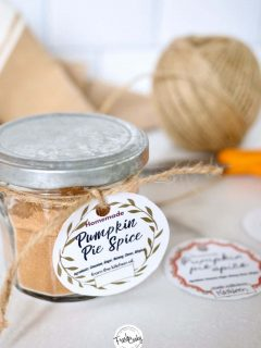image of pumpkin pie spice mix in small jar with silver lid with cute gift tag and other gift tags on marble top with napkin, ball of string and scissors in background.