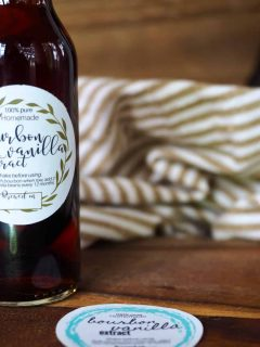 Horizontal image of bottle filled with bourbon vanilla extract with cute label, striped tea towel in background and another label design laying on a cutting board.