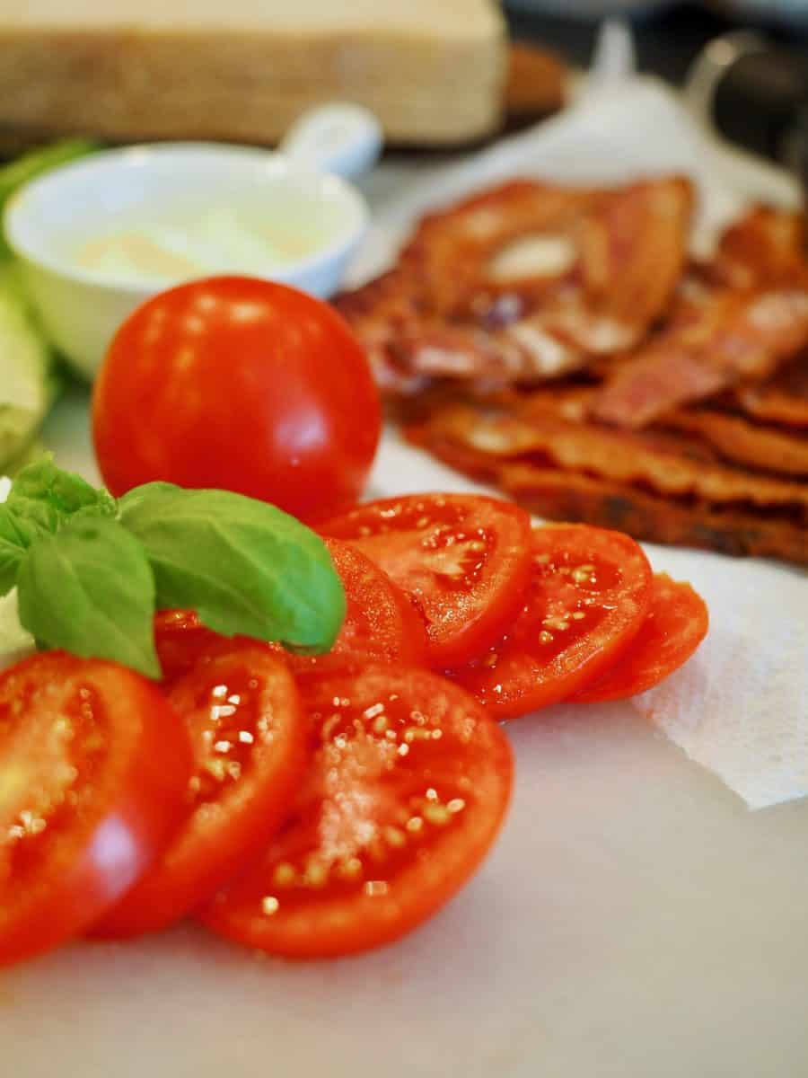 Sliced juicy tomatoes on a cutting board, with a whole tomato behind, fresh basil leaves and in the background crisp bacon and a small white bowl of mayonnaise