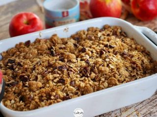 Horizontal image of a white casserole dish filled with baked apple crisp, red apples in the background