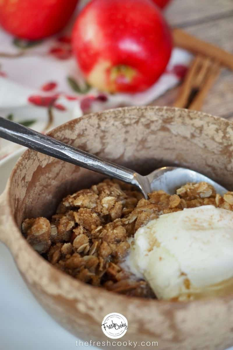 bowl filled with apple crisp and a scoop of vanilla ice cream with apples in background.