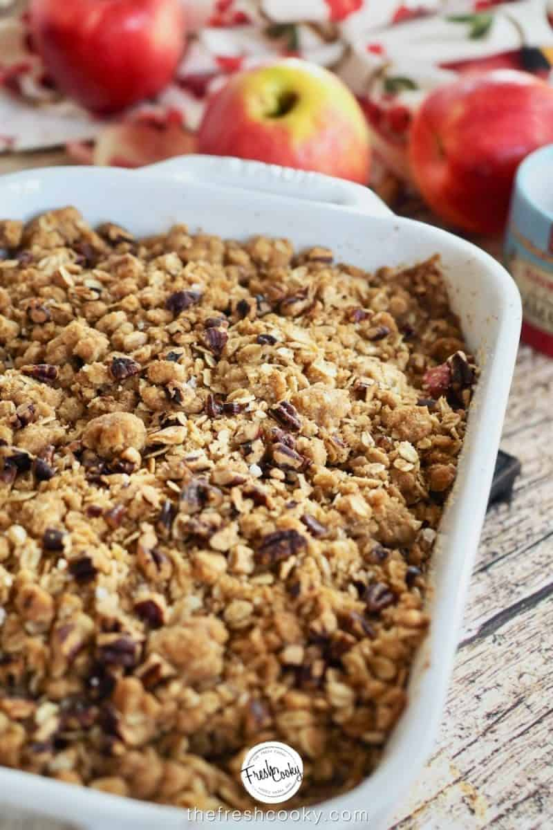 baking dish filled with apple crisp with red apples in background