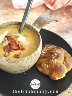 Horizontal image for beer cheese soup with bowl of soup in wooden bowl with spoon on a black plate with soft pretzel beside sitting on a rustic wood surface.