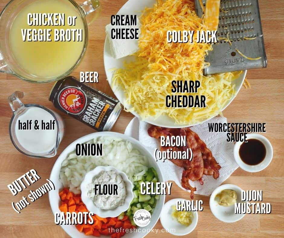 Beer Cheese Soup Ingredients, labeled. Left to right, chicken stock, cream cheese, sharp cheddar cheese white, colby jack cheese, worcestershire sauce, dijon mustard, minced garlic, celery, carrots, onions, flour, butter, half and half, beer and bacon.