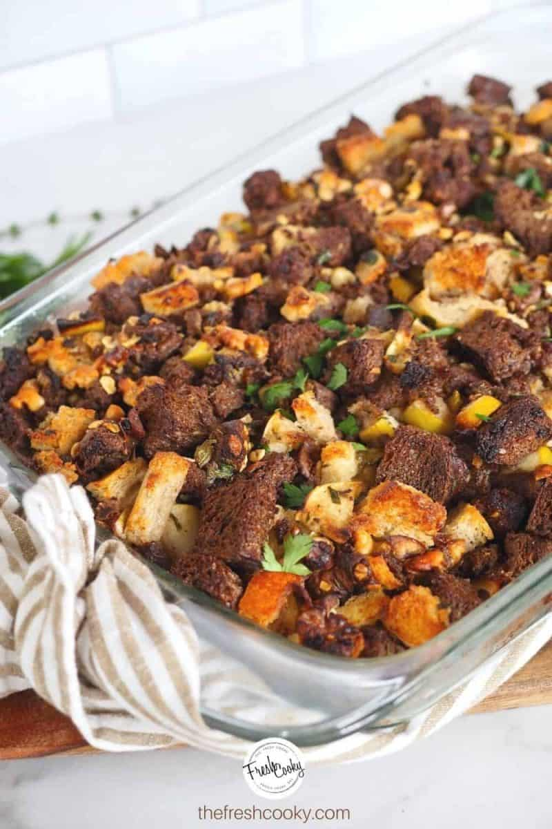 Image of casserole dish filled with the best stuffing ever, a variety of bread types are used with chunks of sausage, nuts, apples and more