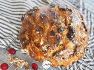 Facebook image of top down shot of artisan cranberry walnut bread loaf on cooling rack with fresh cranberries and walnuts tossed about it. Striped tea towel underneath.