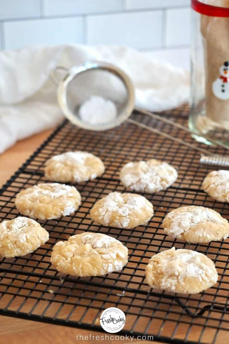 image of 9 eggnog gooey butter cookies on cooling rack with powdered sugar in seive.