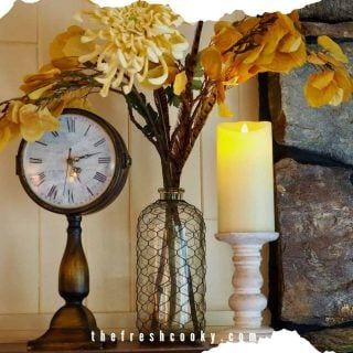 Fall-mantle with old time clock, glas vase witth aspen leaves, giantt mum and rustic candlestick with pillar candle