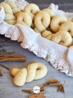 Horizontal image of Koulourakia Greek Butter Cookies in basket with ruffled napkin and one on table with smashed cinnamon sticks