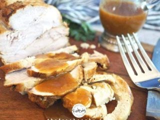 Facebook image of Sliced Turkey Breast on cutting board with pan gravy drizzled on top. Large fork in foreground with pitcher of gravy behind.