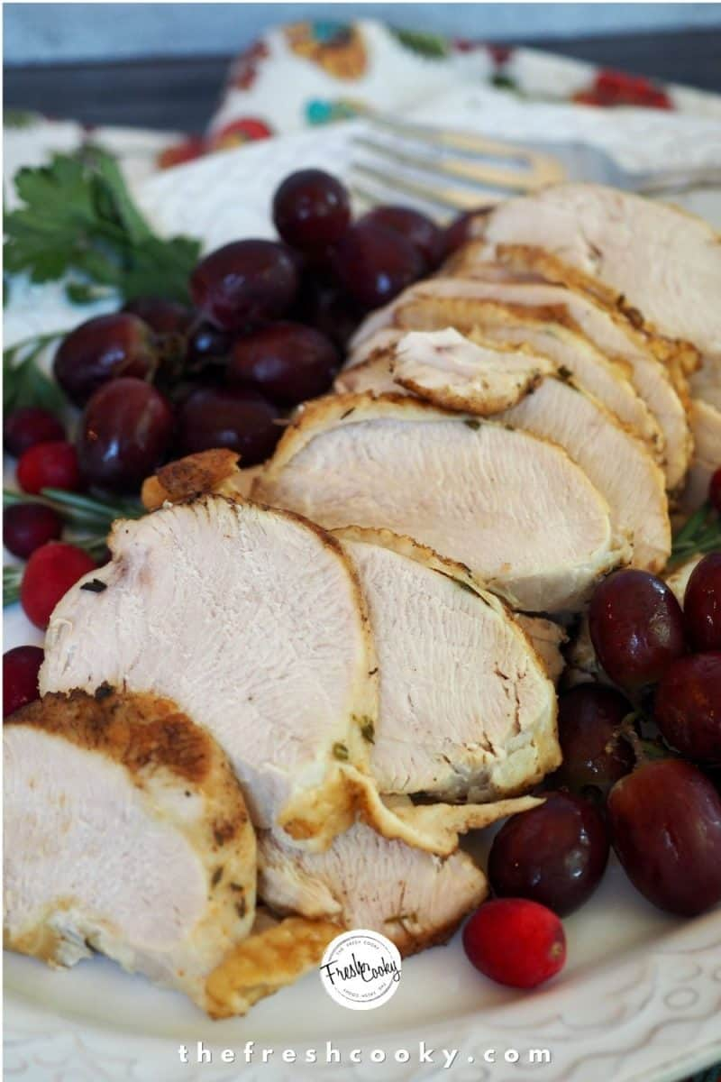 Instant Pot Turkey Breast image with partially sliced turkey breast on platter with cranberries, grapes and fresh herbs surrounding the turkey.