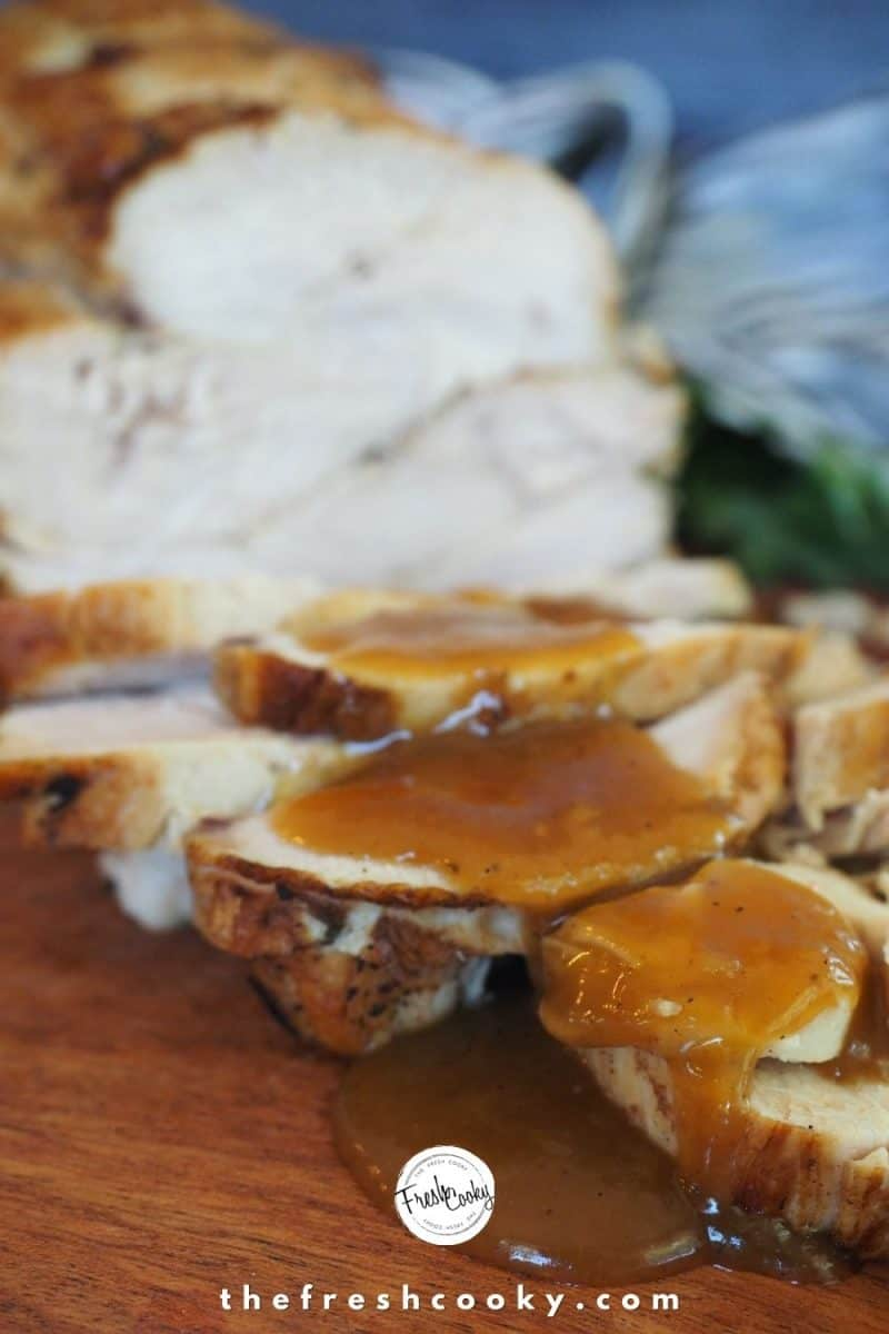 Image of boneless turkey breast, sliced on cutting board with pan dripping gravy poured over a few slices.