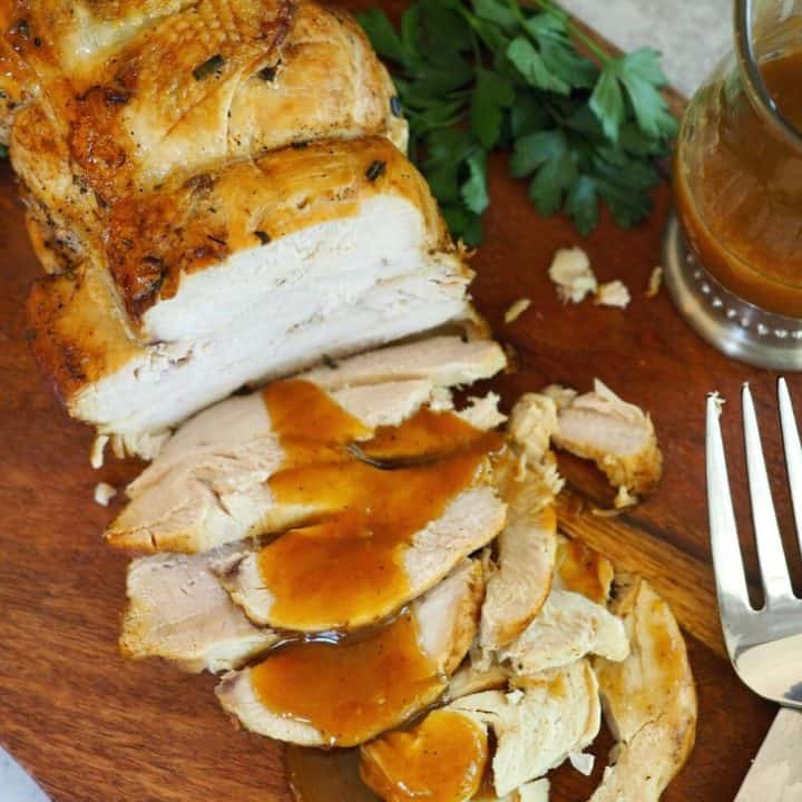 Top down shot of cooked Instant Pot Turkey Breast drizzled with pan gravy, on wooden cutting board.