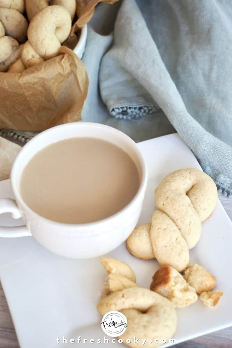 Greek Butter Cookie twists in a square white plate with a cup of tea and additional cookies in background