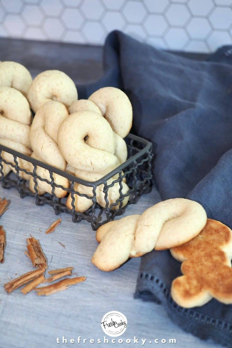 Greek Butter Cookies in wire basket with two laying on counter, one Koulourakia cookie turned upside down to see the browned underside. Cinnamon sticks crushed.