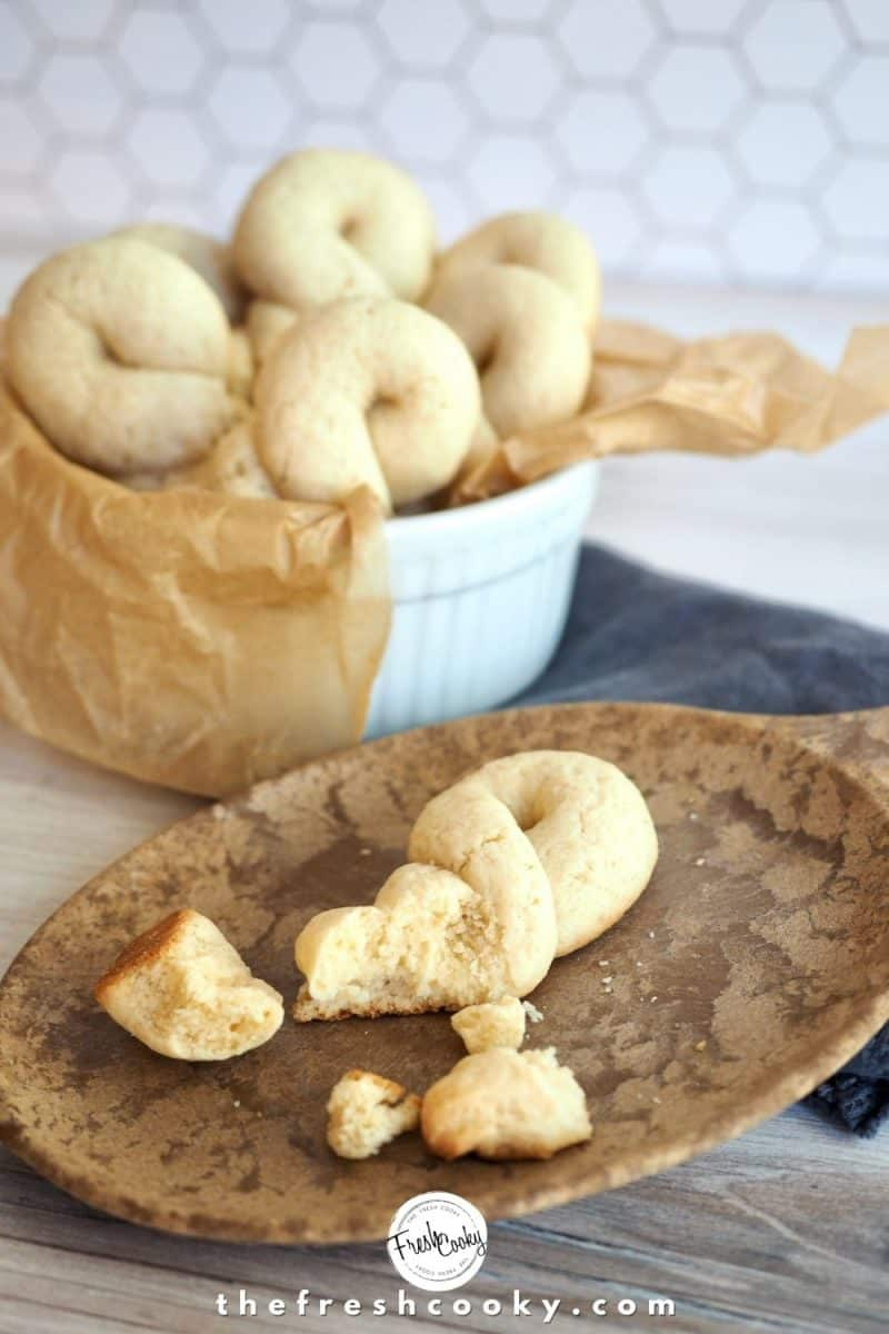 Broken Koulourakia cookie on wooden plate with small bowl lined with parchment behind stuffed with more baked cookies.