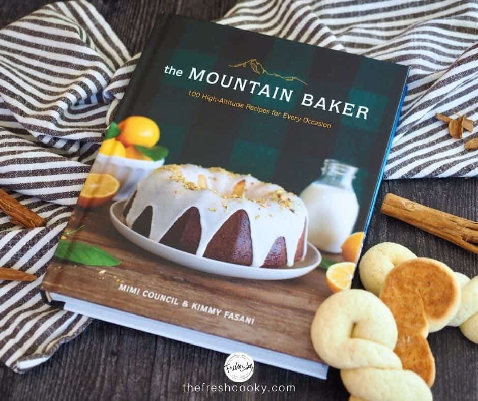 Image of the Mountain Baker Cookbook with homemade Koulourakia Greek Butter Cookies sitting near, cinnamon sticks and a striped tea towel