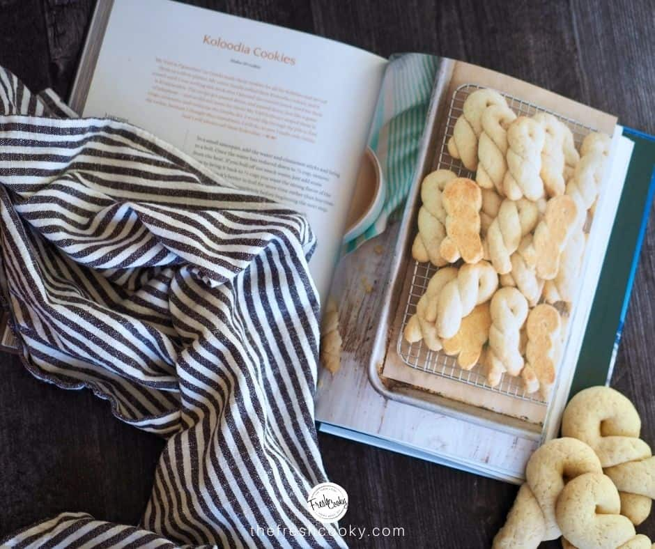 Cookbook open to recipe for Koloodia cookies with a striped tea towel laying on top and real Koulourakia cookies to the right of the cookbook
